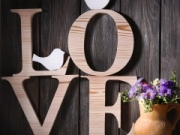 Decorative letters forming word LOVE with wildflowers on wooden background